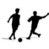 Sylwetki gracze piłki nożnej z piłką Fotografia Stock
