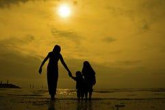 Sylwetki grupa dzieciaki bawić się przy plażą Zdjęcia Royalty Free