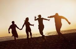 Sylwetki grupują przyjaciół zaludniają plaża bieg zmierzch Obraz Stock