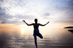 Sylwetki kobiety ćwiczy joga na zmierzch plaży Obrazy Royalty Free