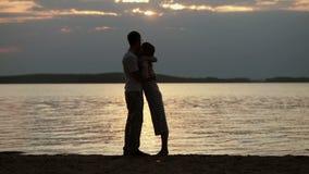 Sylwetki kochankowie przy zmierzchem Młody piękny pary obejmowanie na brzeg jezioro zdjęcie wideo
