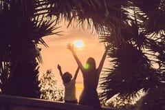 Sylwetki które spotykają zmierzch w zwrotnikach przeciw tłu drzewka palmowe matka i syn, zdjęcie stock