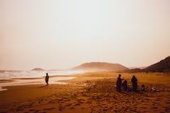 Sylwetki ludzie bawić się w piaskowatej Złotej plaży, Karpasia, Cypr obrazy royalty free