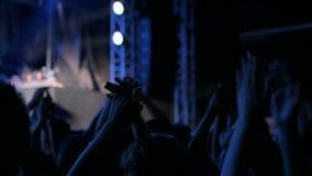 Sylwetki ludzie bawi się i klascze przy rockowym koncertem przed sceną zdjęcie wideo