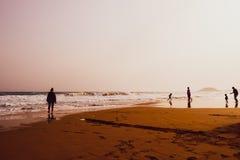 Sylwetki ludzie bawi? si? w piaskowatej Z?otej pla?y, Karpasia, Cypr fotografia stock
