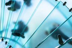 Sylwetki ludzie chodzi na szklanym ślimakowatym schody Zdjęcia Royalty Free