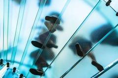 Sylwetki ludzie chodzi na szklanym ślimakowatym schody Zdjęcia Stock