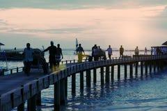 Sylwetki ludzie na drewnianym moscie nad morzem tropikalna wyspa, Zdjęcia Stock