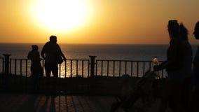 Sylwetki ludzie na ulicie Zmierzch przy morzem Zapętlający wideo zdjęcie wideo
