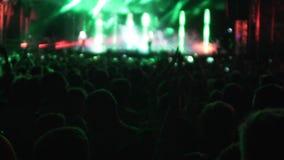 Sylwetki ludzie ogląda występ piosenkarzem, jaskrawi światła na scenie zdjęcie wideo