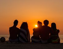 Sylwetki ludzie siedzi na plaży Zdjęcia Stock
