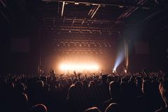 Sylwetki ludzie w jaskrawym w wystrzału rockowym koncercie przed sceną Ręki z gestów rogami Ten skały Przyjęcie w a Zdjęcie Royalty Free