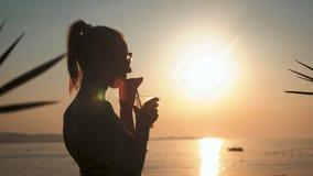 Sylwetki młoda kobieta pije koktajl na plaży przy zmierzchem na tle zbiory
