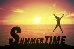 Sylwetki młoda kobieta skacze up jej rękę o szczęśliwym pojęciu na lato czasu tekscie i podnosi obraz stock