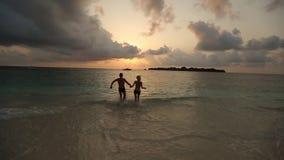 Sylwetki młoda szczęśliwa para biega zmierzch w oceanu mienia rękach w zwolnionym tempie Dwa kochanka na miesiącu miodowym zdjęcie wideo