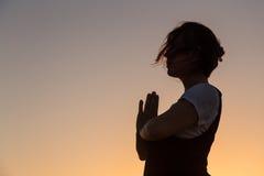 Sylwetki młodej kobiety ćwiczy joga na plaży przy zmierzchem obrazy royalty free