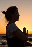 Sylwetki młodej kobiety ćwiczy joga na plaży przy zmierzchem obraz stock