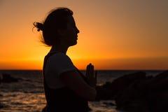 Sylwetki młodej kobiety ćwiczy joga na plaży przy zmierzchem obrazy stock