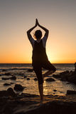 Sylwetki młodej kobiety ćwiczy joga na plaży przy zmierzchem obraz royalty free