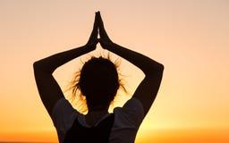 Sylwetki młodej kobiety ćwiczy joga na plaży przy zmierzchem fotografia royalty free