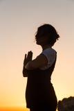 Sylwetki młodej kobiety ćwiczy joga na plaży przy zmierzchem zdjęcia royalty free