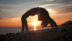 Sylwetki m?odej kobiety ?wiczy joga przy zmierzchem na morzu Szcz??liwi momenty ?ycie - sylwetki joga na pla?y na zbiory