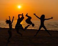 Sylwetki młodzi ludzie ma zabawę na plaży obrazy royalty free