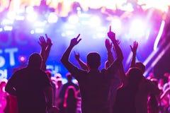 Sylwetki młodzi ludzie podczas jaskrawego występu, festiwal muzyki Obraz Stock