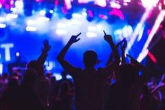Sylwetki młodzi ludzie podczas jaskrawego występu, festiwal muzyki Fotografia Stock