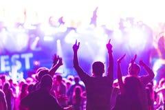 Sylwetki młodzi ludzie podczas jaskrawego występu, festiwal muzyki Zdjęcie Royalty Free