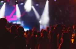 Sylwetki młodzi ludzie podczas jaskrawego występu, festiwal muzyki Obraz Royalty Free
