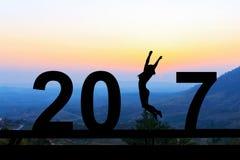 Sylwetki młoda kobieta skacze nad 2017 rok na wzgórzu przy su Zdjęcia Stock