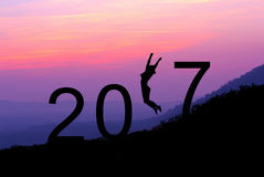 Sylwetki młoda kobieta skacze nad 2017 rok na wzgórzu przy su Fotografia Stock