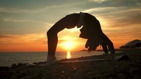 Sylwetki m?odej kobiety ?wiczy joga przy zmierzchem na morzu Szcz??liwi momenty ?ycie - sylwetki joga na pla?y na zbiory wideo