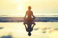 Sylwetki medytaci kobieta na tle zmierzch i morze Fotografia Stock