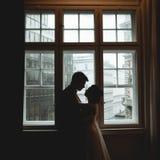 Sylwetki nowożeńcy stoi w przodzie jaskrawy windo Zdjęcie Royalty Free