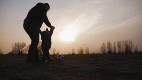 Sylwetki ojcują i mały syn z piłką bawić się piłkę nożną na łące przy zmierzchu czasem Pojęcie życzliwa rodzina zdjęcie wideo