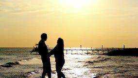Sylwetki para Blisko morza przy zmierzchem Embransing i całowaniem zbiory