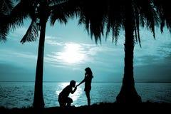 Sylwetki para, kobieta stojak i mężczyzna, siedzimy na podłoga, chwyt i całujący jej rękę dla proponuje ona poślubiać przed morze Zdjęcia Stock