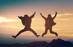 Sylwetki pary kochankowie skaczą zdjęcie royalty free