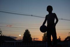 Sylwetki piłka i chłopiec Fotografia Royalty Free