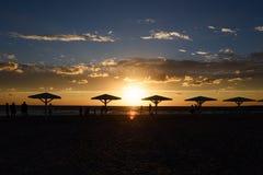 Sylwetki plażowi parasole przy zmierzchem fotografia stock