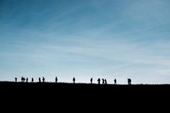 Sylwetki podróżnicy na wzgórzu z niebieskim niebem Zdjęcia Stock