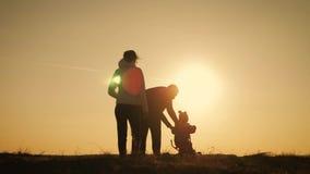Sylwetki rodzina jest wpólnie przy zmierzchem Młody chłopiec uczenie jechać bicykl, ojciec uczy jego syna jechać rower w zbiory