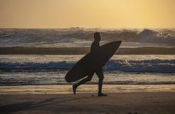 Sylwetki surfingowiec przy zmierzchem na plaży zdjęcia stock