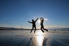 Sylwetki szczęśliwi młodzi ludzie skacze nad lodem jeziorny Baikal przy zmierzchem obrazy royalty free