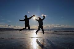 Sylwetki szczęśliwi młodzi ludzie skacze nad lodem jeziorny Baikal przy zmierzchem fotografia royalty free