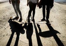 Sylwetki trzy przyjaciół deskorolkarze w mieście Fotografia Stock
