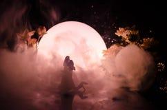 Sylwetki zabawkarski para taniec pod księżyc przy nocą Postacie mężczyzna i kobieta w miłości tanczy przy blaskiem księżyca Fotografia Royalty Free