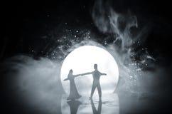 Sylwetki zabawkarski para taniec pod księżyc przy nocą Postacie mężczyzna i kobieta w miłości tanczy przy blaskiem księżyca Fotografia Stock
